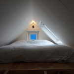 De slaaploft met het bed en de ramen aan het einde